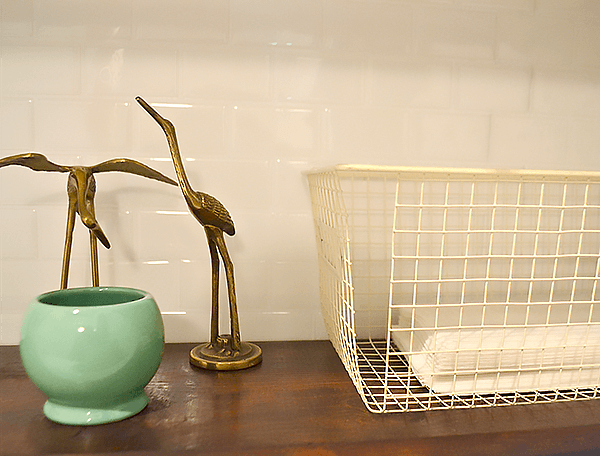Vignette with thrifted finds, brass cranes, green catch-all dish