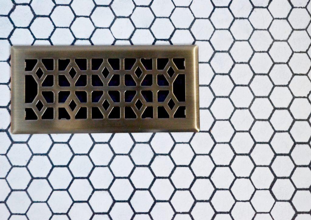 stenciled tile floors, hex tile black and white floors, modern geometric floors with brass floor vent