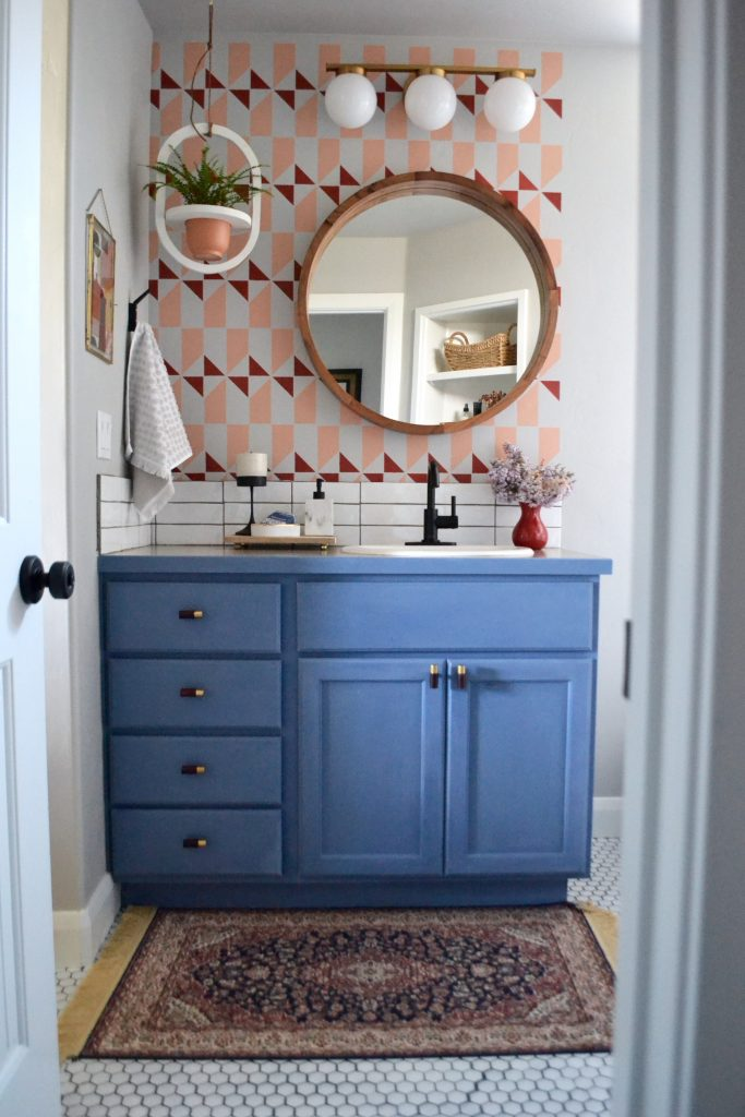 eclectic master bathroom, geometric stenciled wall behind blue chalk paint vanity, round mirror, round midcentury light fixture, hanging planter, blue and red color scheme, vintage rug