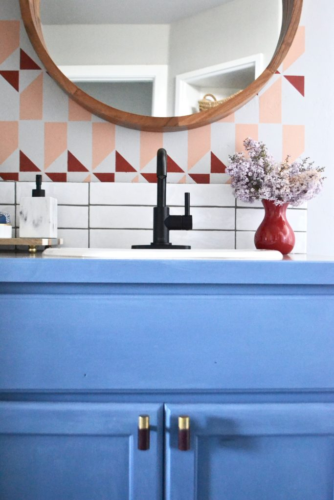geometric stencil, peach and red, round wooden mirror, matte black faucet, blue cabinets