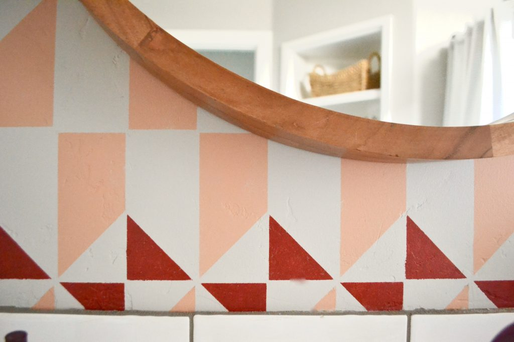 geometric stencil in bathroom, red and peach color scheme, wood round mirror